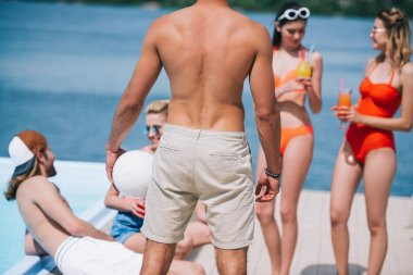 back view of man holding ball and spending time with friends at poolside