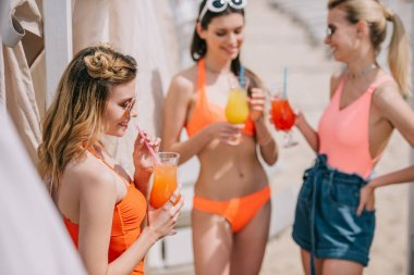 beautiful young women in swimwear drinking cocktails on beach