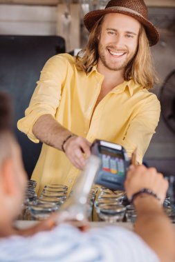 selective focus of young man paying with credit card at beach bar