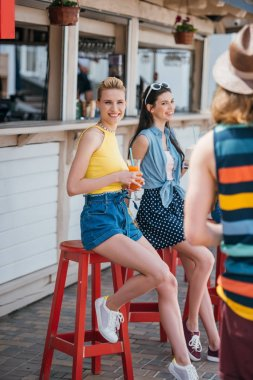 beautiful young woman holding cocktail and smiling at camera while spending time with friend at beach bar