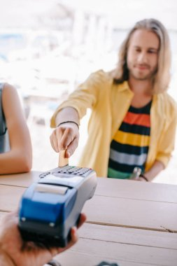 Selective focus of young man paying with credit card on terminal at beach bar stock vector