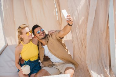 happy young couple in sunglasses taking selfie with smartphone in bungalow