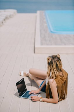 high angle view of girl using laptop with black screen at poolside