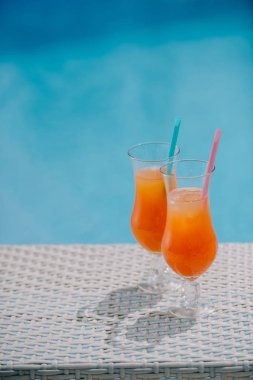 close-up view of summer cocktails with drinking straws at pool