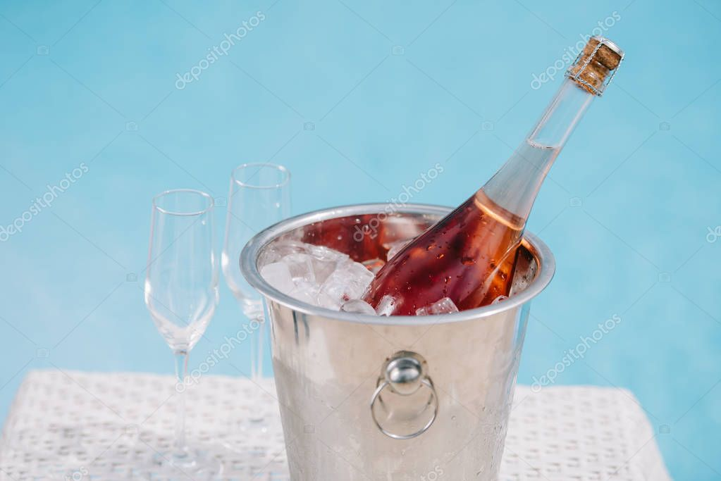 bottle of champagne in bucket with ice and two empty glasses at poolside