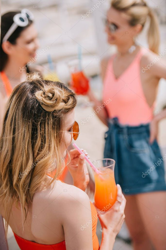 young woman drinking summer cocktail while spending time with girlfriends on beach