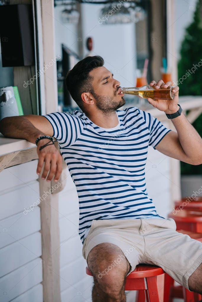 handsome young man drinking beer from glass bottle while sitting at beach bar