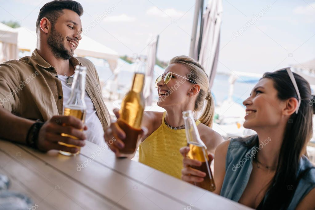 happy young man looking at beautiful smiling girls and drinking beer together at beach bar
