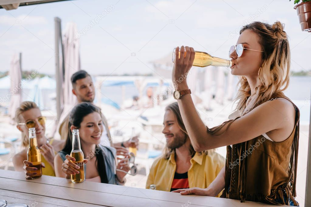 happy young male and female friends drinking beer at beach bar