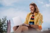 nízký úhel pohledu usměvavý mladý muž pomocí přenosného počítače na pláži