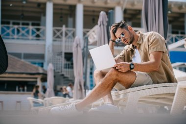 handsome young man in sunglasses using laptop while resting on chaise longue