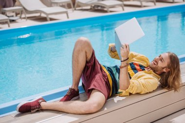 smiling young man using laptop while lying near pool