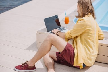young man using laptop with blank screen while sitting at poolside