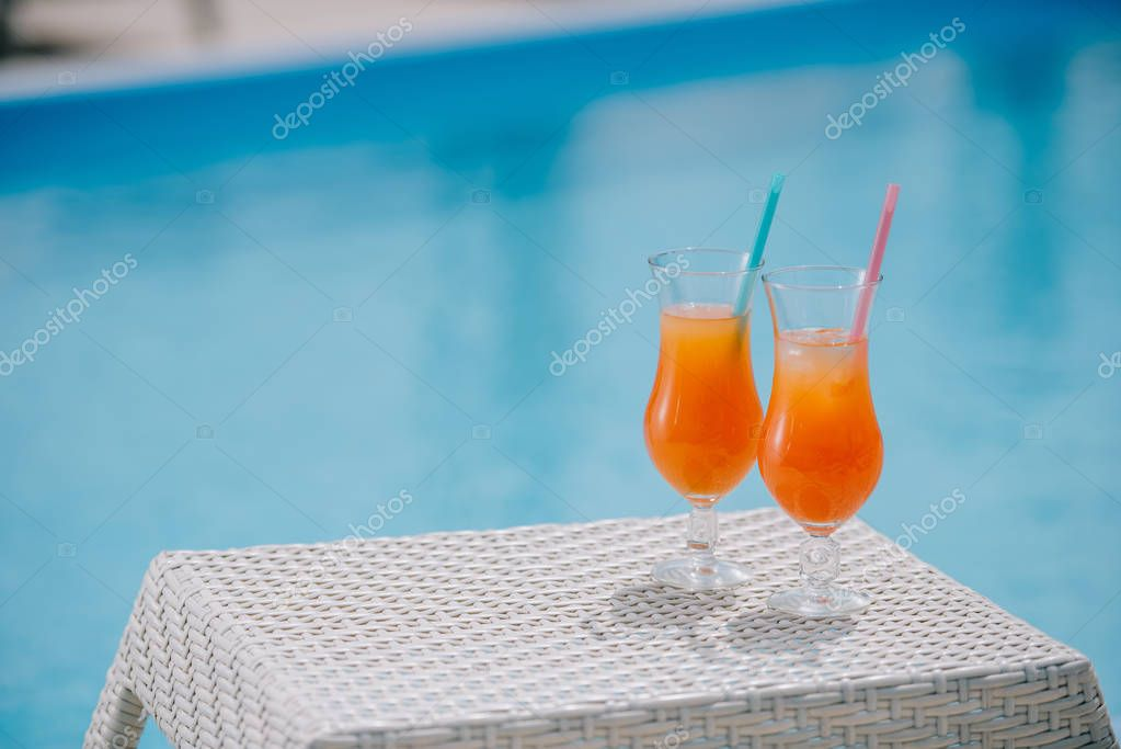 close-up view of summer cocktails with straws at poolside