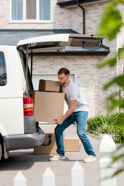 focused young man moving boxes from car into new house