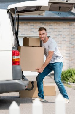 smiling young man moving boxes from car into new house