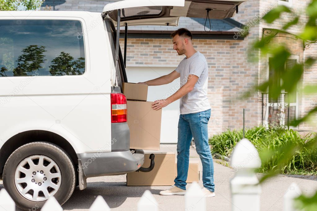 side view of young man moving boxes from car into new house
