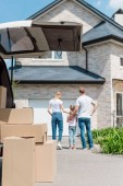 Photo close up shot of cardboard boxes in car trunk and family with daughter looking at new house