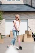 Fotografie šťastné dětství jízda na koloběžka poblíž boxy a akustickou kytaru před nový dům
