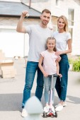 man holding key with trinket while his wife embracing daughter on kick scooter in front of new house