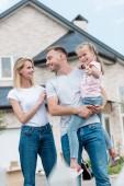 žena všeobjímající manžel, zatímco on drží dcera inf průčelí nového domu