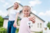 Nahaufnahme des Schlüssels mit Schmuckstück in der Hand des Kindes an Hand der Mutter vor neue Hütte