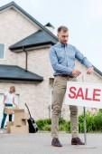 Fotografie männliche Grundstücksmakler hängen verkaufsschild vor der Verpackung Kartons für die Verlagerung von Haus Frau