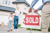 Fotografia vista parziale dellagente immobiliare appeso ha venduto il segno nella parte anteriore della gente che si muove nella nuova casa