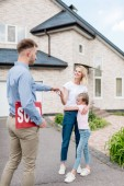 smiling male realtor with sold sign giving key to young woman with daughter in front of new house