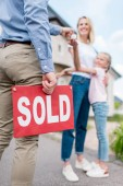 Fotografie cropped image of realtor with sold sign giving key to young woman with daughter in front of new house