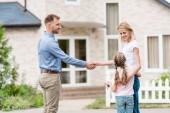 Fotografia vista laterale dellagente immobiliare che agita la mano di giovane donna con la figlia davanti alla nuova casa