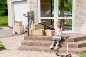 Fényképek gyermek használ laptop közelében dobozok, gitár és kick robogó lépcsőn új ház