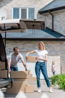 couple carrying cardboard boxes for relocation into new house and their daughter riding on kick scooter behind