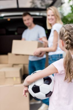 cropped shot of little child holding soccer ball while her parents unpacking cardboard boxes for relocation