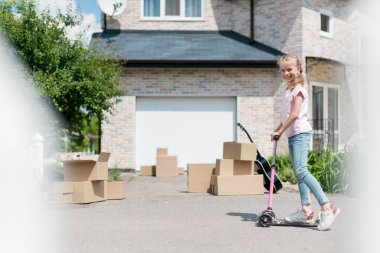 smiling child riding on kick scooter near boxes and acoustic guitar in front of new house