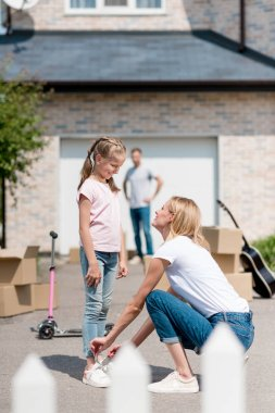 smiling woman tying shoelaces of daughter and man standing behind near cardboard boxes in yard of new cottage
