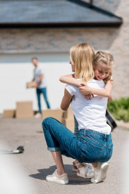 back view of woman hugging smiling daughter and man unpacking cardboard boxes behind in yard of new house