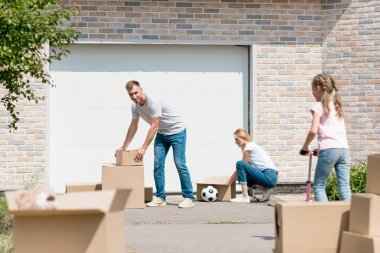 young couple unpacking cardboard boxes while their daughter riding on kick scooter in front of new cottage