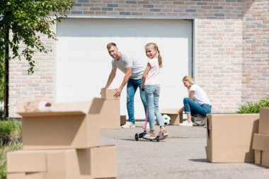 couple unpacking cardboard boxes while their daughter riding on kick scooter in front of new cottage