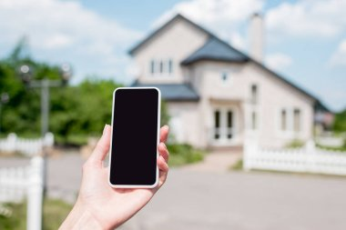 cropped image of young woman holding smartphone with blank screen in front of house