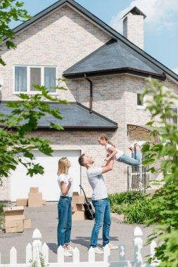 side view of father raising up daughter while mother standing near in front of their new house