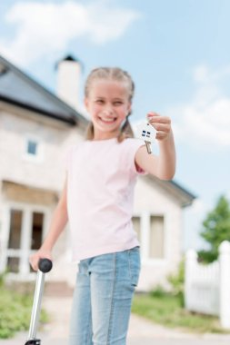 smiling child with on kick scooter holding key with trinket near new house