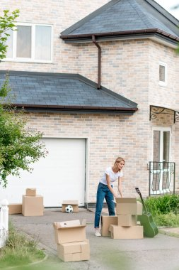 young woman unpacking cardboard boxes near guitar in front of new cottage