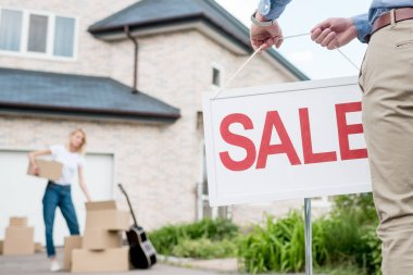 cropped image of male realtor hanging sale sign in front of woman packing cardboard boxes for relocating from house