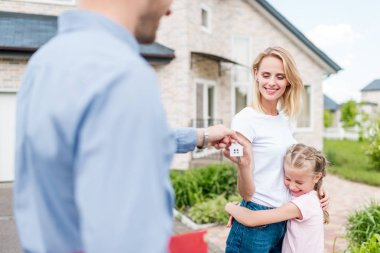 partial view of real estate agent giving key to young woman with daughter in front of new house