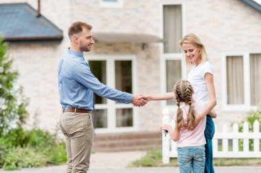 side view of realtor shaking hand of young woman with daughter in front of new house
