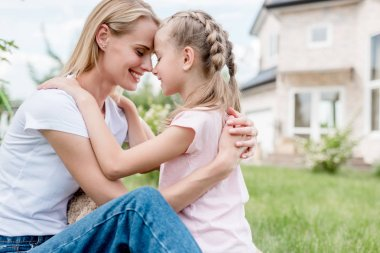 side view of happy child sitting forehead to forehead with smiling mother