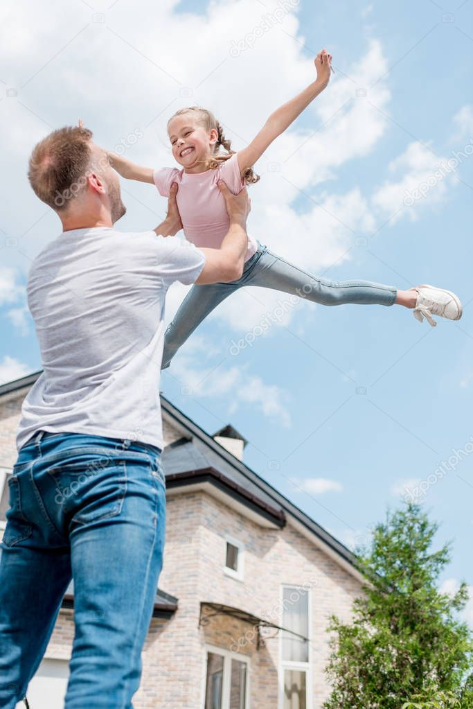 low angle view of father raising up smiling daughter with wide arms in front of house