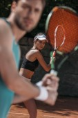 junge hübsche Mann und Frau spielen Tennis als Team