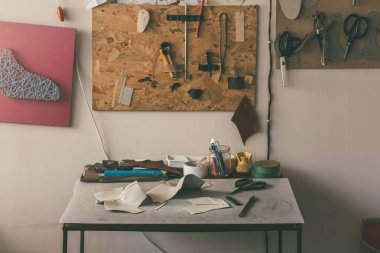 table with leather samples and various tools with scissors at shoemaker workshop